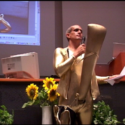 THE-YES-MEN-speaker-nextgengallery-Andy-Bichlbaum-with-Golden-Phallus-suit-eviltwinbookingdotcom-400x400_c